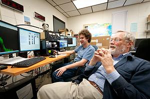 MSU freshman Matthew Handley, left, and SSEL Director David Klumpar watch as information is downloaded from MSU's orbiting satellite. (MSU photo by Kelly Gorham)