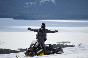 Business owner Rick Vancleeve enjoys a moment of exuberance while on a snowmobile trip over the Montana countryside.